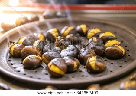 Close Up Of Roasted Chestnuts For Sale On The Street In Winter. Street Food Concept.