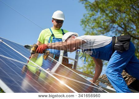 Two Professional Technicians Connecting Solar Photo Voltaic Panel To Metal Platform Using Screwdrive