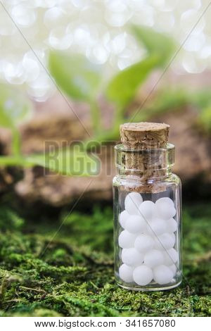 Homeopathic Globules In Glass Bottle, Close-up On A Natural Background, On Moss, Against A Backgroun
