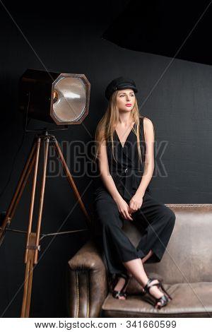 Blonde Model Posing In Dark Studio. Young Attractive Fashion Model Posing On Dark Background