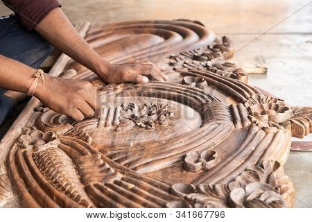 Beautiful Carved Woodwork In An Indian Street Workshop. The Hands Of An Indian Carpenter Polishing T