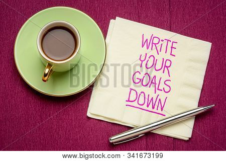write your goals down reminder - handwriting on a napkin with a cup of coffee, planning, setting and recording goals concept
