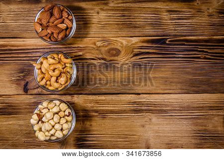 Various Nuts (almond, Cashew, Hazelnut) In Glass Bowls On Wooden Table. Vegetarian Meal. Healthy Eat