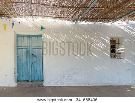 Blue Wooden Door, Small Window And Straw Roof With Dramatic Light Rays And Shadows At Abadoned Churc