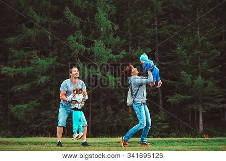 Young Family With Children Playing Near The Forest