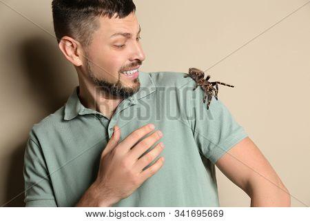Scared Man With Tarantula On Beige Background. Arachnophobia (fear Of Spiders)