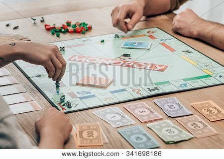 Kyiv, Ukraine - November 15, 2019: Cropped View Of Man And Women Playing Monopoly Game At Table