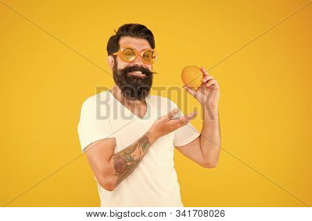 His Diet Plan. Bearded Man Pointing At Orange On Yellow Background. Hipster Choosing Citrus Fruit Fo