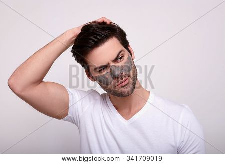Male Wearing A Charcoal And Bentonite Clay Face Mask Beauty Treatment. Front Portrait Of A Male Wear