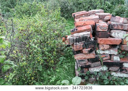 Pile Of Stacked Rows Of Old, Cracked, Burnt Bricks In An Abandoned, Unkempt, Overgrown Garden In Sum