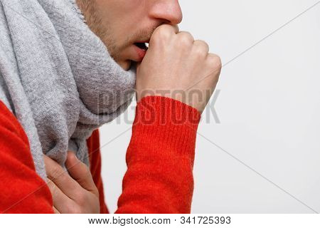 Close Up Of Unhealthy Man In Orange Sweater Suffering With Pulmonary Cough Due To Cold, Flu, Respira