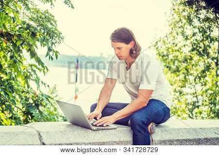 Young American Man With Long Dark Brown Hair Working On Laptop Computer Outside In New York City, We