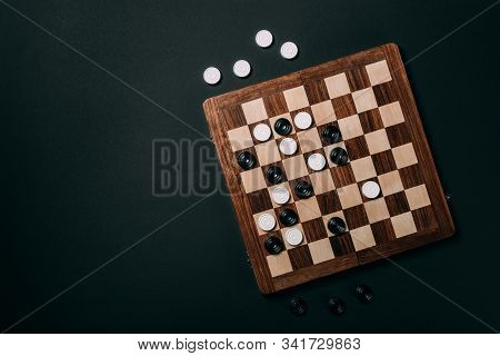 Top View Of Checkers On Wooden Checkerboard Isolated On Black With Copy Space
