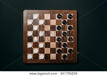 Top View Of Checkers On Wooden Checkerboard Isolated On Black
