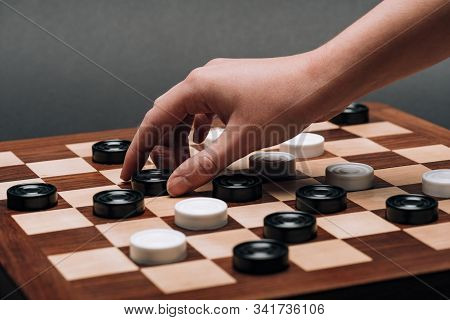 Cropped View Of Woman Holding Checker On Wooden Checkerboard On Grey Background