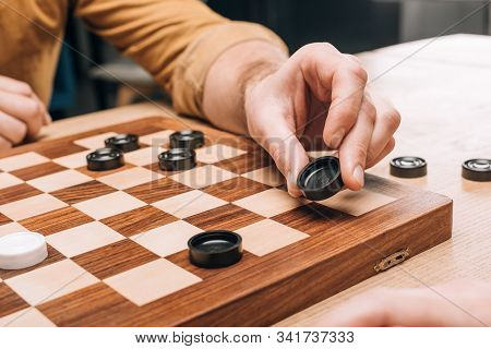 Selective Focus Of Man Holding Black Checker On Wooden Checkerboard