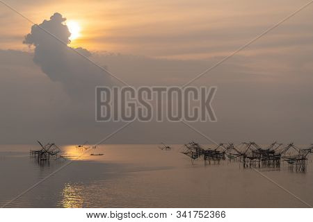 Thai Traditional Bamboo Fishing Tools With Unidentified Silhouette People On Boat During Sunrise In