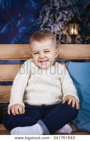 Small Infant Boy Wearing Sweater And Jeans Sitting On The Wooden Bench Near A Blue Pillow Indoor