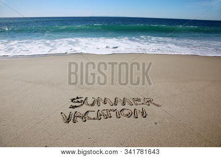 Summer Vacation. The word SUMMER VACATION written in the sand on the beach. Laguna Beach California. Words written in sand.