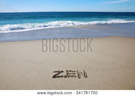 Zen. The word ZEN written in beach sand in Laguna Beach California. Pacific ocean with waves and blue sky background. Words in sand.