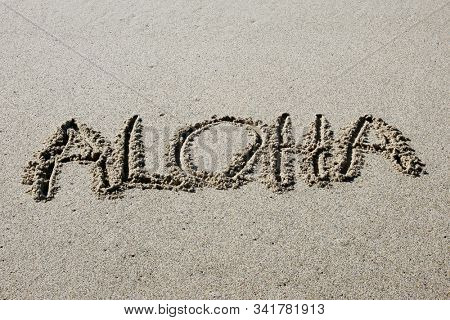 Words written in sand. Aloha written in sand on the beach. Hawaiian words written in beach in Hawaii. Vacation travel location.  Pacific Ocean with blue tide and waves.