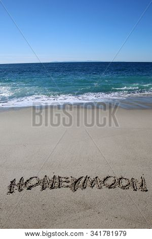 Words written in sand. HONEYMOON written in the sand on the beach. Hawaiian beach with the Pacific Ocean background and the word HONEYMOON written in the sand. Hawaii is a Honeymoon destination.