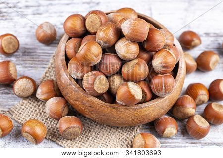 Top View Of Hazelnuts With Peeled Hazelnuts In Brown Bowl On Textured Wooden Background.