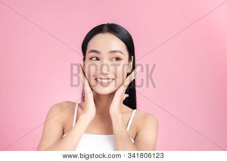 Beautiful Young Asian Girl Touching Her Perfect Skin On Pink Background. Skin Care Concept