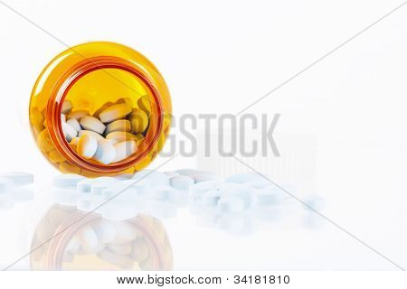 Pills Spilling From Bottle With Reflections On White Background