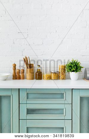 Modern White And Turquoise Kitchen Interior With Kitchenware, Food Containers And Plant Near Brick W