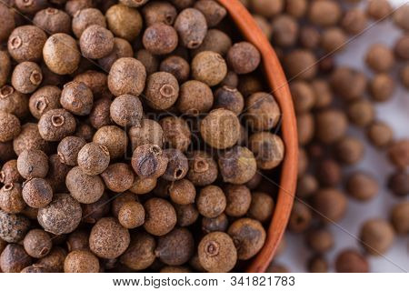 Fresh Spicy Peppers Allspice On White Acrylic Background