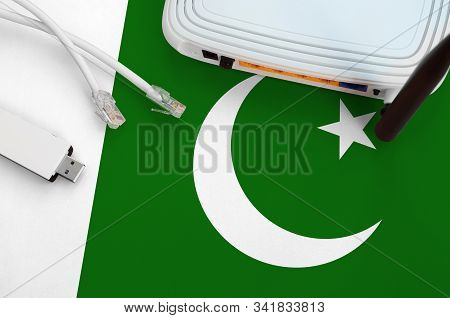 Pakistan Flag Depicted On Table With Internet Rj45 Cable, Wireless Usb Wifi Adapter And Router. Inte