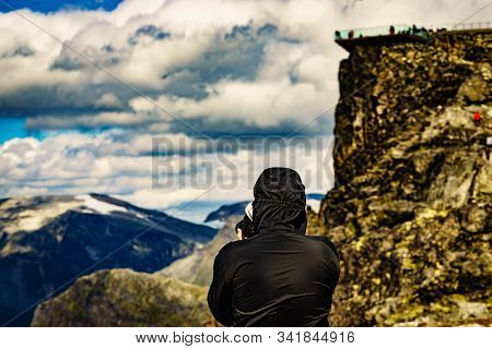 Tourist Taking Photo With Camera, Enjoying Mountains Landscape From Dalsnibba Area In Norway. People
