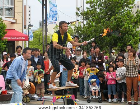 Osaka, Japan - May 03, 2009:  The Juggler With Burning Torches Entertains Passersby And Tourists On