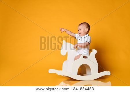 Playful Frolic Infant Baby Boy Toddler In White Bodysuit Is Riding His Wooden Horse For Children And