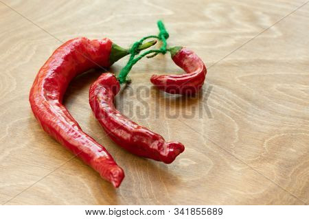 Dried Red Hot Chili Pepper As Spicy Flavoring For Meal. A Group Of Bright Red Thai Chili Peppers Wit