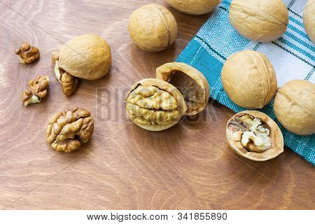 Whole Walnuts And Walnut Kernel Halves Without Shell On A Dark Wooden Table And Checkered Towel, Clo