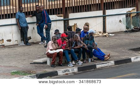 Johannesburg, South Africa - October 2019: Group Of People In Johannesburg Sitting Together By The R