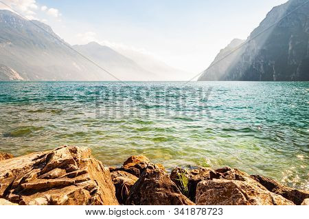 Rocky Stones Lying On The Shore Of Beautiful Garda Lake In Lombardy, Italy Surrounded By High Dolomi