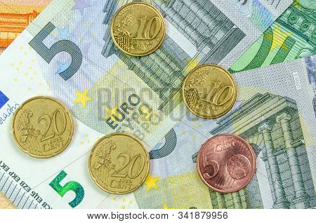 5, 10 And 20 Euro Cents Lie On The Background Of Euro Banknotes. Change Concept. Inflation