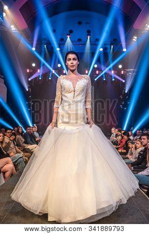 LJUBLJANA, SLOVENIA - OCTOBER 12, 2019: Fashion model in a wedding dress walking down the runway at the Wedding fair
