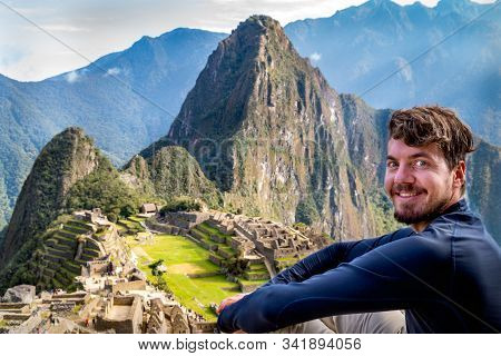 A Man Posing In Machu Picchu. You Can See The Ruins Of The Citadel Of Machu Picchu, The Huayna Picch