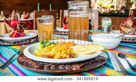 Delicious Beef With Mango Sauce, Served With Fries And Vegetables. Brown Traditional Amazonian Drink