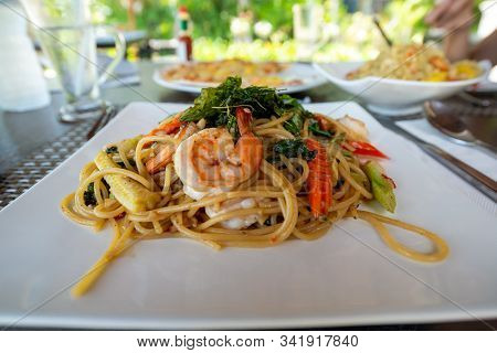 Thai Style Spaghetti (pad Kee Maw) With Shrimp, Corn, Carrot, And Fried Basil In The White Plate, Fu