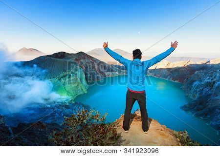 At Sunrise Man Stand On Rock Above Volcano Kawah Ijen Crater. Look At Largest In World Sulphur Acid