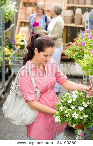 Young woman holding white surfinia flower at garden center store