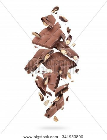Pieces Of Chocolate Bar With Nuts Falling Down On White Background