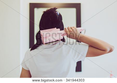 Woman Using Electric Curling Iron With Hair On Front Of Mirror,straightening Hair,straightener,curly