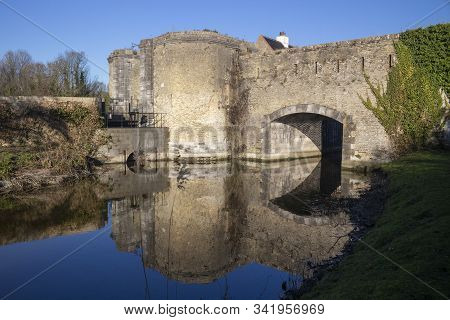 Reflections Of The Ramparts At Bergues, Northern France, Against A Blue Sky.