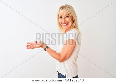 Middle age woman wearing casual t-shirt standing over isolated white background pointing aside with hands open palms showing copy space, presenting advertisement smiling excited happy